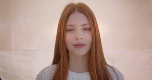 Retrato do modelo bonito do gengibre que sorri modestamente na câmera no fundo branco da parede video estoque