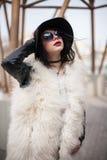 Retrato do modelo bonito no casaco de pele, no chapéu e nos óculos de sol Urb Imagens de Stock