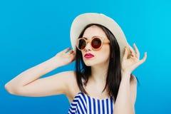 Retrato do modelo fêmea em óculos de sol da forma e em chapéu do verão no fundo azul foto de stock royalty free