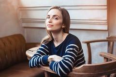 Retrato do moderno fêmea de sorriso que espera encontrando o melhor amigo quando durante a ruptura de café no café cinzento Imagem de Stock