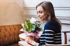Retrato do moderno fêmea de sorriso que senta-se no café e que guarda o ramalhete da mola Presente da flor do noivo cinzento Imagens de Stock
