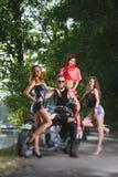 Retrato do motociclista e de três meninas 'sexy' Fotografia de Stock Royalty Free