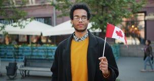 Retrato do movimento lento do ar livre afro-americano farpado do homem com bandeira canadense filme