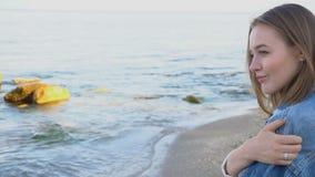 Retrato do movimento lento da fêmea bonito que respira o ar e as poses de mar fresco com sorriso, suporte contra o mar azul e céu vídeos de arquivo