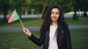 Retrato do movimento lento da jovem mulher bonita alegre do fã de esportes que acena a bandeira portuguesa, olhando a câmera e o  filme