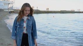 Retrato do movimento lento da jovem mulher bonito que levanta e sorri in camera, estando na praia do mar no dia de verão fresco filme