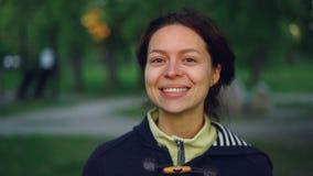 Retrato do movimento lento da jovem mulher encantador que veste a roupa ocasional que está fora no parque e na vista de sorriso filme