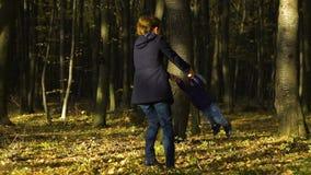 Retrato do movimento lento da mãe nova feliz que afaga seu filho do bebê no parque do outono filme