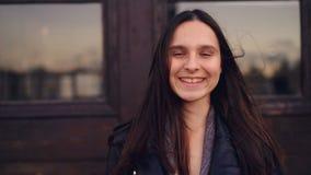 Retrato do movimento lento da morena bonita da menina com o cabelo longo que olha a câmera com estar então de sorriso reto da car vídeos de arquivo