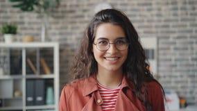 Retrato do movimento lento da posição de sorriso da jovem senhora atrativa no escritório moderno