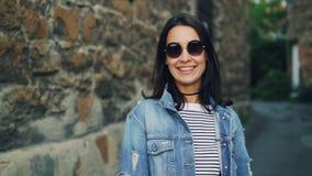 Retrato do movimento lento da senhora atrativa em óculos de sol na moda e na roupa à moda que estão fora com paredes de pedra den video estoque