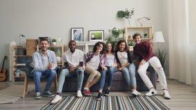 Retrato do movimento lento das meninas e dos indivíduos que correm ao sofá que senta-se olhando a câmera vídeos de arquivo