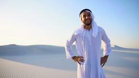 Retrato do movimento lento do xeique árabe dos UAE do indivíduo muçulmano bonito em Kandura no meio do deserto sem fundo em ensol video estoque