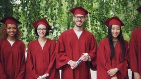 Retrato do movimento lento dos graduados nas almofariz-placas e dos vestidos que olham a câmera, sorrindo e guardando diplomas hi video estoque
