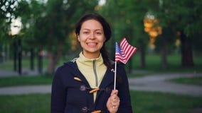 Retrato do movimento lento do fã americano da jovem senhora bonita que olha a câmera e a bandeira de ondulação de sorriso do Esta filme