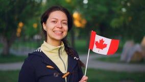 Retrato do movimento lento do fã de esportes canadense da menina atrativa que guarda a bandeira nacional de Canadá e que olha a c filme