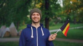 Retrato do movimento lento do homem belga no revestimento e no chapéu de esportes que guardam a bandeira nacional de Bélgica com  filme