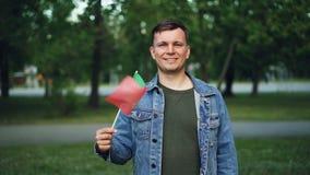 Retrato do movimento lento do homem considerável na roupa ocasional que acena a bandeira portuguesa com sorriso feliz e que olha  vídeos de arquivo