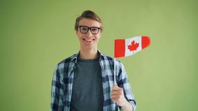 Retrato do movimento lento do partiot masculino que guarda a bandeira canadense e o sorriso filme