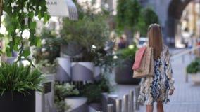Retrato do movimento lento do passeio shopaholic de sorriso da mulher na rua com sacos de papel, de girar e de olhar a câmera filme