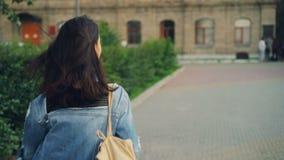 Retrato do movimento lento do viajante encantador da jovem senhora que corre ao longo da estrada na cidade então que gira e que o video estoque
