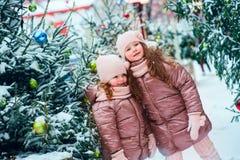 Retrato do Natal de um jogo feliz de duas irmãs exterior na cidade nevado do inverno decorada por feriados do ano novo imagens de stock