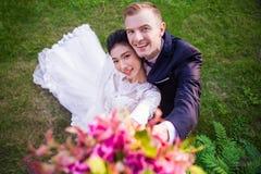 Retrato do ângulo alto de pares felizes do casamento no campo gramíneo Imagem de Stock Royalty Free