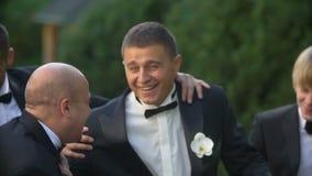 Retrato do noivo feliz que tem o divertimento com seus três melhores homens ao andar ao longo do parque filme