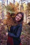 Retrato do outono da mulher menina bonito fora com um ramalhete da samambaia amarela na floresta, conceito da queda do outono imagem de stock