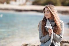 Retrato do outono de uma mulher bonita na costa de mar fotografia de stock