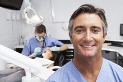 Retrato do paciente dental de With Dentist Examining da enfermeira no fundo imagens de stock royalty free