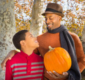 Retrato do pai afro-americano considerável e do filho feliz que escolhem uma abóbora no outono foto de stock royalty free