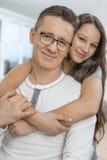 Retrato do pai de abraço da menina afetuosa de trás em casa imagens de stock royalty free