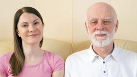 Retrato do pai e da filha nova que relaxam no sofá em casa Família feliz que aprecia o tempo junto filme