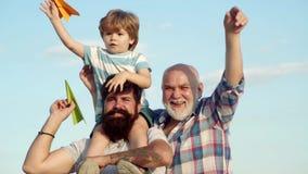 Retrato do pai feliz que d? o passeio do reboque do filho em seus ombros e que olha acima Conceito da inf?ncia Feriado da fam?lia filme