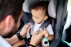 Retrato do pai novo que fixa o bebê no assento da criança do carro fotografia de stock