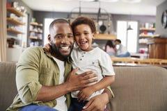 Retrato do pai And Son Sitting em Sofa In Lounge Together fotografia de stock royalty free