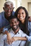 Retrato do pai superior de sorriso With Adult Son e da filha que abraça em casa imagem de stock royalty free