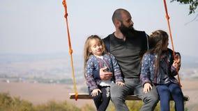 Retrato do paizinho que balança com filhas em um balanço sob uma árvore filme