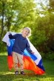 Retrato do parque bonito do verão do rapaz pequeno em público com a bandeira do russo no fundo Criança dos fãs que apoia e que ch foto de stock royalty free