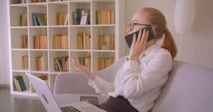 Retrato do perfil do close up da mulher de negócios loura caucasiano bonita nova nos vidros usando o portátil e tendo um telefone filme