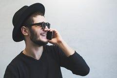 Retrato do perfil de rir o indivíduo novo que que usa o smartphone sobre o fundo branco Óculos de sol e chapéu vestindo, vestidos fotografia de stock