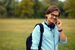Retrato do perfil de um estudante novo do smilig que fala no smartphone, em um fundo do parque público, com espaço da cópia imagem de stock