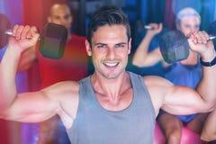 Retrato do peso de levantamento de sorriso do homem no gym Fotos de Stock Royalty Free