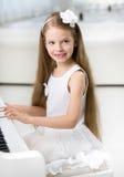 Retrato do pianista pequeno no vestido branco que joga o piano Fotografia de Stock