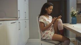 Retrato do pijama vestindo de sorriso da mulher afro-americana nova que senta-se na mesa de cozinha em casa e que datilografa em  video estoque