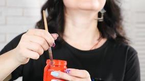 Retrato do pintor fêmea feliz com o frasco de vidro com pintura vermelha nela Gota da pintura da escova Pintura nas aquarelas video estoque