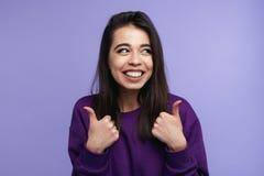 Retrato do polegar na moda da exibição da jovem mulher acima sobre o fundo violeta foto de stock royalty free