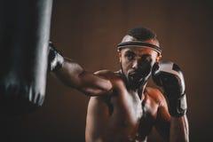 Retrato do pontapé praticando tailandês muay concentrado do lutador no saco de perfuração Imagem de Stock