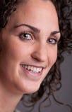 Retrato do primeiro plano de uma mulher de cabelo encaracolado de sorriso Imagem de Stock Royalty Free